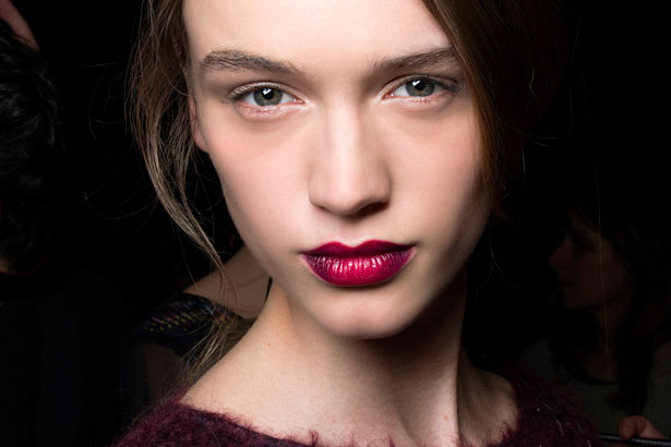 model with subtle face makeup and dark fuschia lipstick