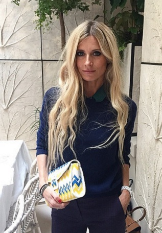 Laura Bailey pose with a clutch from her LK Bennett collaboration