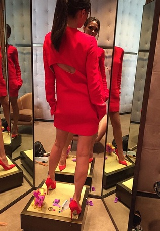 Victoria Beckham poses in mirror in red dress