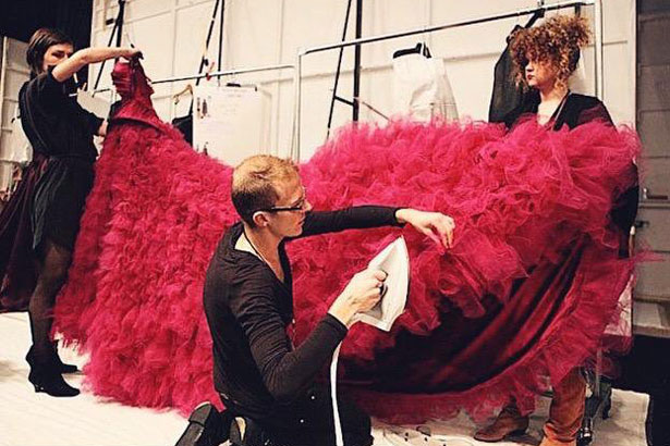 stylists prepping red Christian Siriano gown