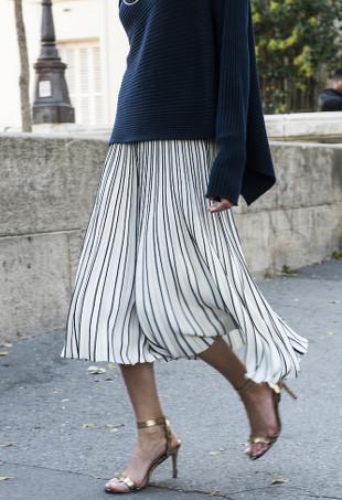 A woman wearing a white pleated skirt, navy sweater, and gold sandals.