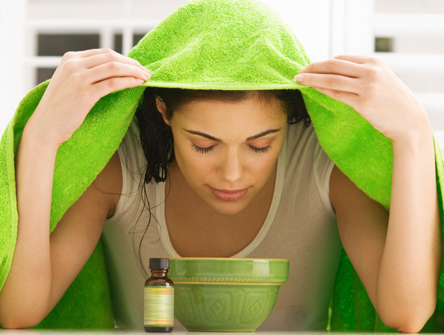 woman showing how to steam your face using a towel and bowl of hot water