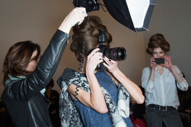 model taking photos backstage at fashion show