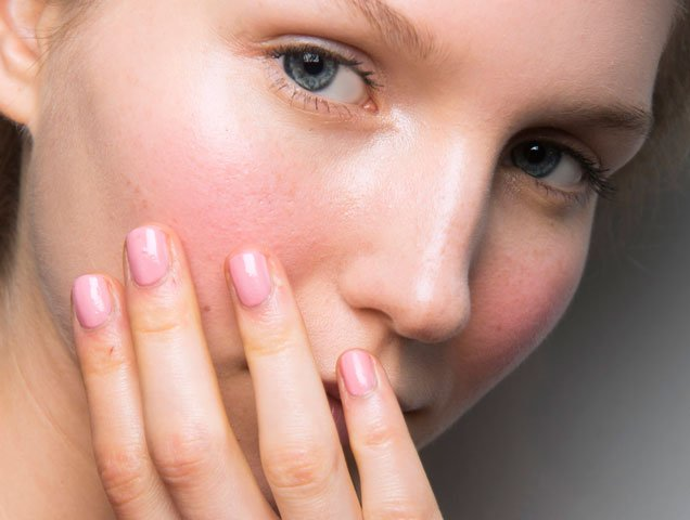 woman looking at skin to find adult acne causes