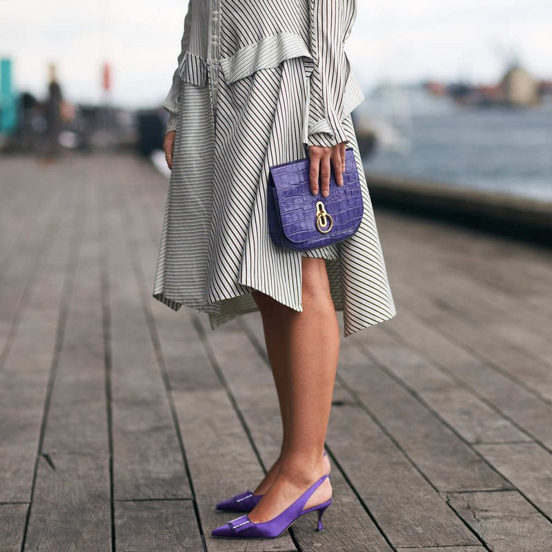 ca4b6148ce3 woman wearing a dress with purple kitten heel slingbacks and a purple bag